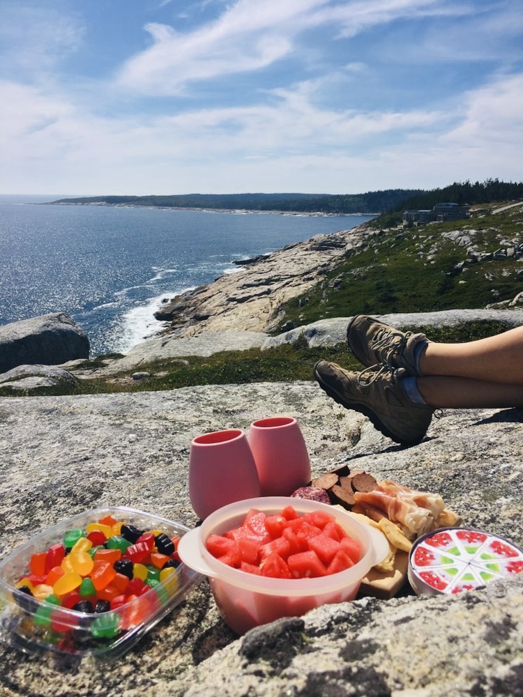 A summer picnic on a granite cliff overlooking the Atlantic ocean at a top Halifax hiking spot.