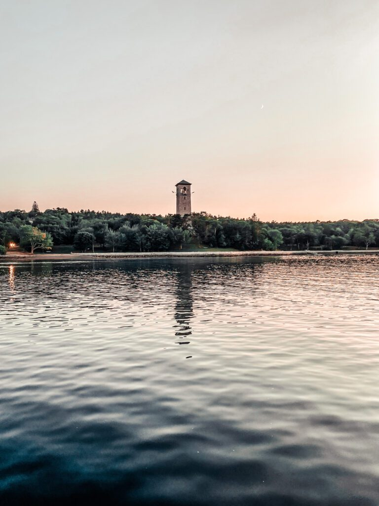 The Dingle Tower pictured at a distance across the lake in the late evening.