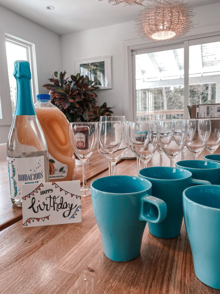 Wine glasses and mugs arranged on a wooden table along with a birthday card, bottle of wine and orange juice at this luxury staycation.