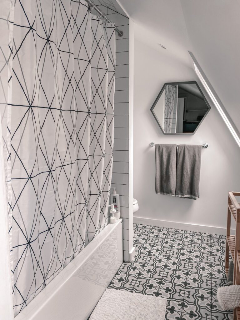 A beautifully-designed bathroom with geometric grey and white patterns throughout at this luxury staycation.