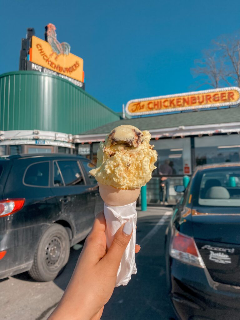 A hand holding an ice cream cone outside of The Chickenburger in Bedford, NS.