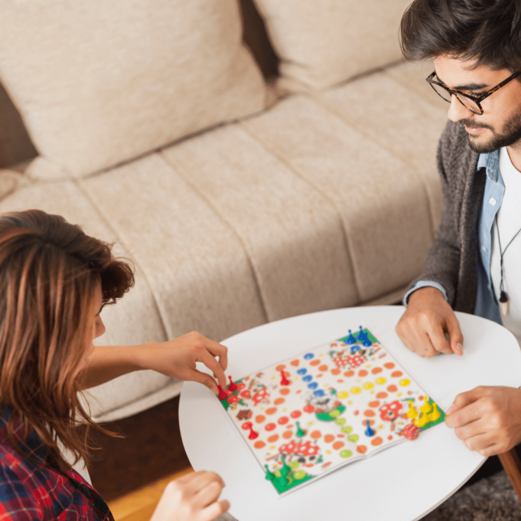 A man and a woman playing a board game together for date night.