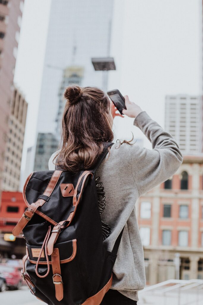 A Calgary tourist taking a photo of the buildings downtown