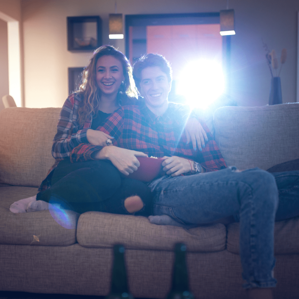 A smiling couple embracing each other, eating popcorn and enjoying a movie for a date night.