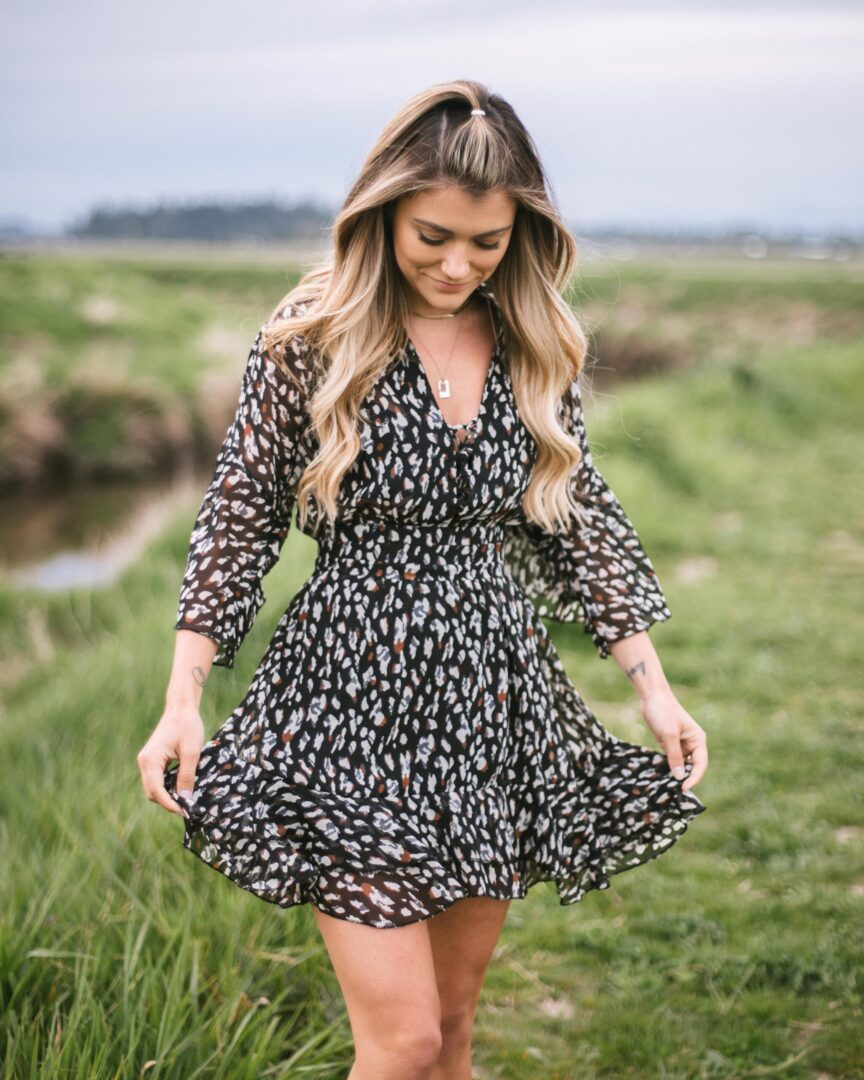 A girl wearing a black spotted dress. She has long blonde wavy hair. The grass is very green in the back ground and the sky is a grey blue colour.