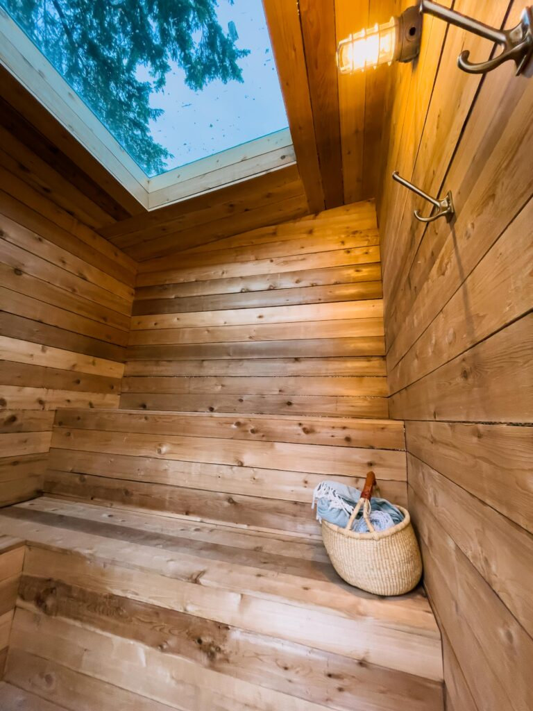 Inside the sauna at Tin Can Ranch. There is a small straw bag with towels and a huge skylight in the top. The back wall has two levels of benches.