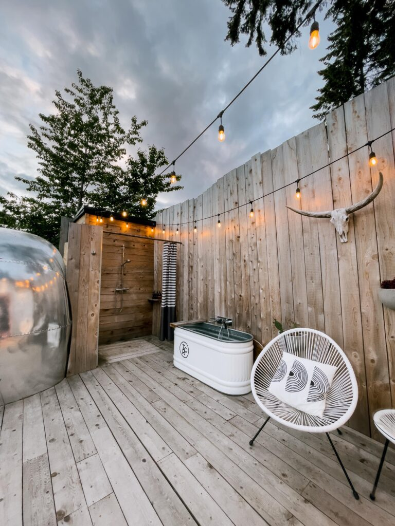 A view of the outdoor shower, metal bathtub, and seating area next to the airstream at Tin Can Ranch