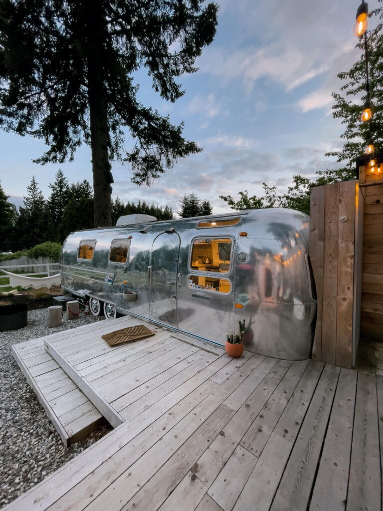 The view of the airstream at Tin Can Ranch from the deck that connects the outdoor shower, bath tub and sauna. off to the left is the fire pit and horseshoe game. The airstream is super shiny and the inside lights are glowing.