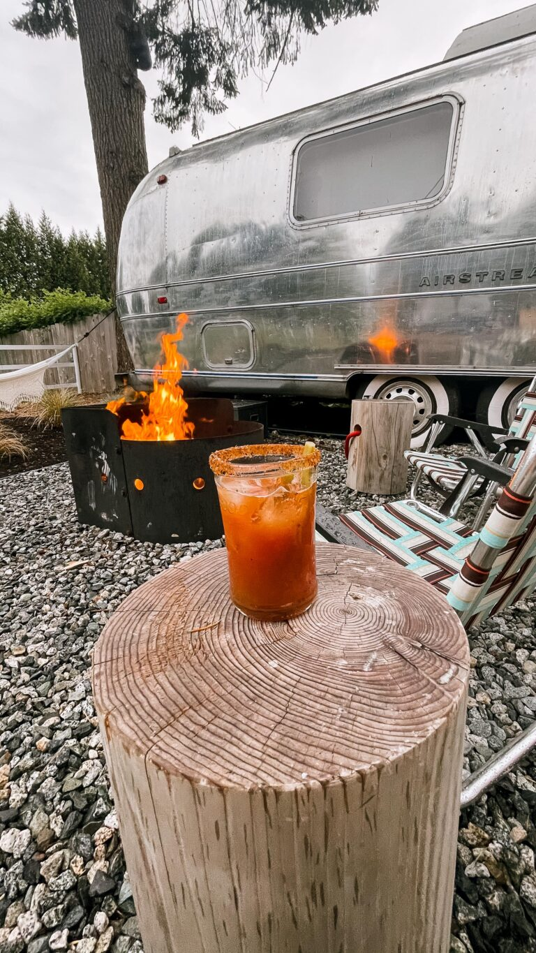 View of the fire pit next to the airstream at Tin Can Ranch with caesar front and centre on the log side table. The fire is burning high and is reflecting in the shiny airstream