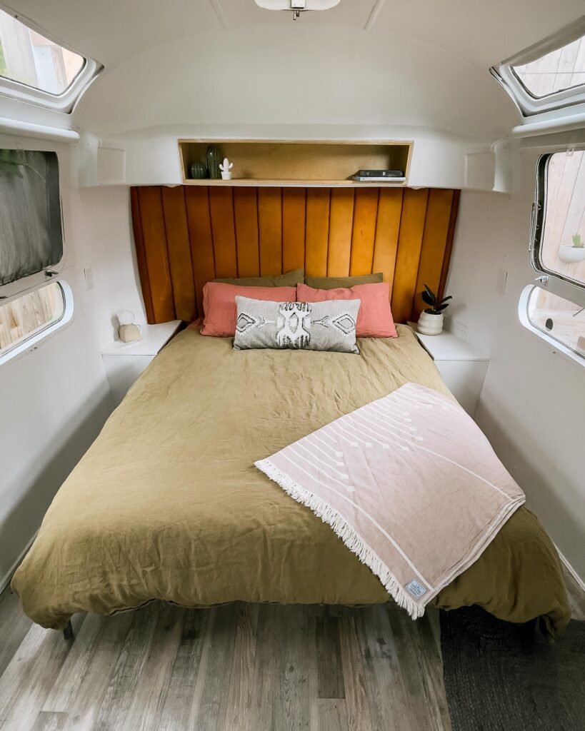 A view of the bed at Tin Can Ranch inside of the airstream. The bedding is a light frost green colour and the pillows are a pink salmon colour. The head board is a dark tan colour.