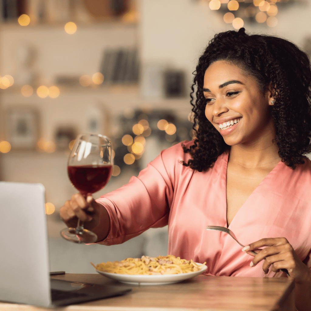 Woman smiling while having dinner during one of her virtual first dates.