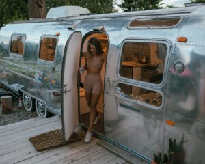 A girl is walking out of the Tin Can Ranch Airstream. It is almost dark out as the sun is going down. The airstream is very shinny.