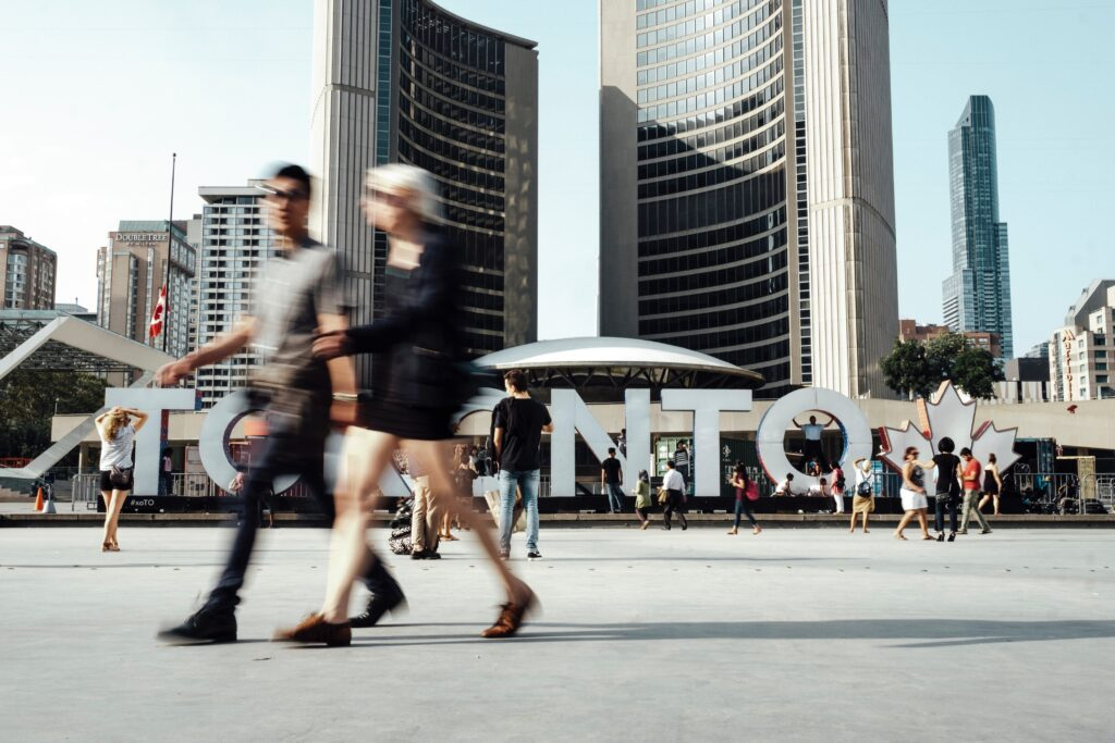 People walking past a large TORONTO sign in Nathan Philip's Square