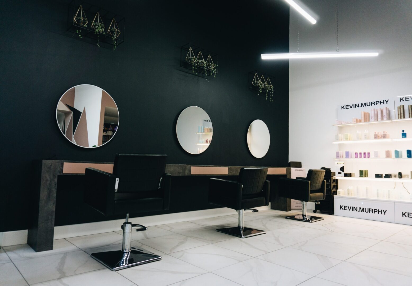 inside of a hair salon, chairs lined up in a row infront of mirrors