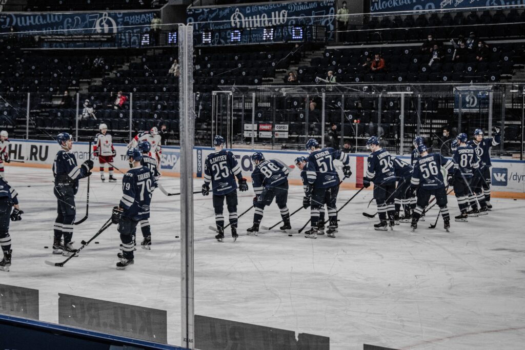 A low angle of a line up of hockey players. They are waiting for the game to start on the ice.