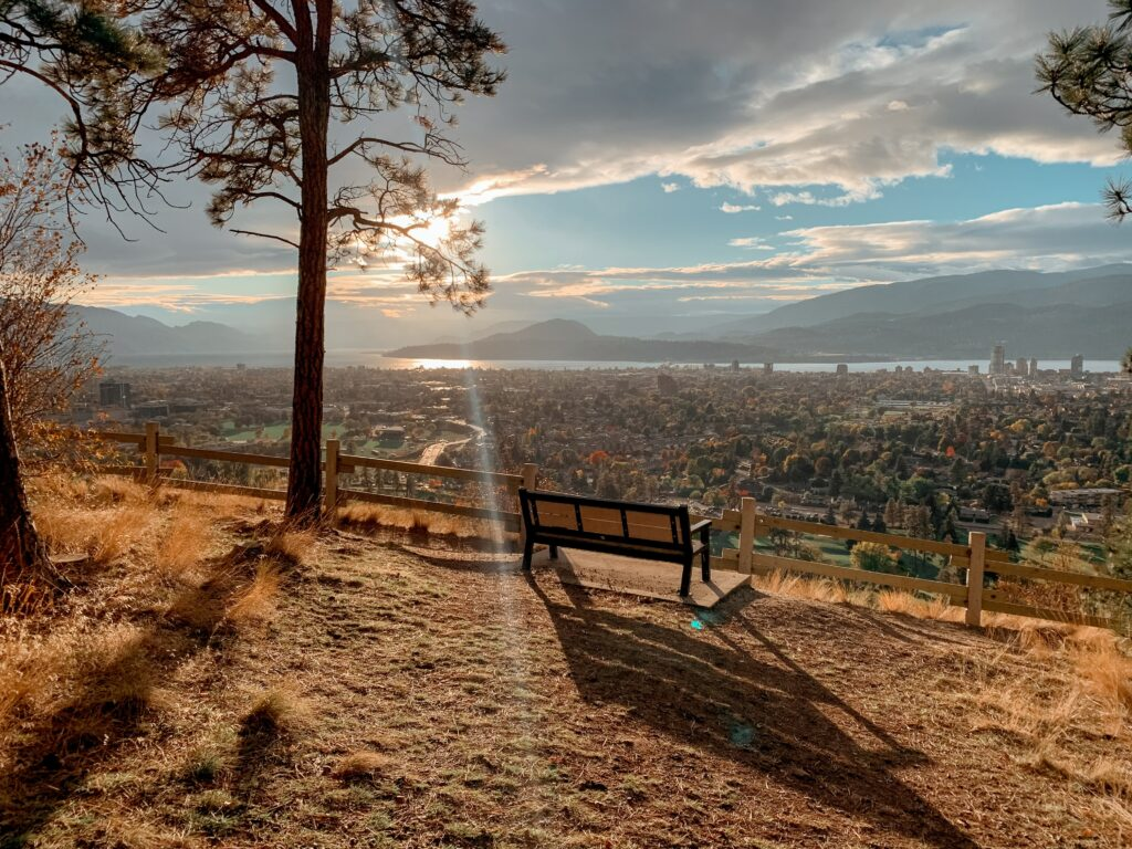 A park bench overlooking Kelowna. The sky is blue and the clouds are rolling in.