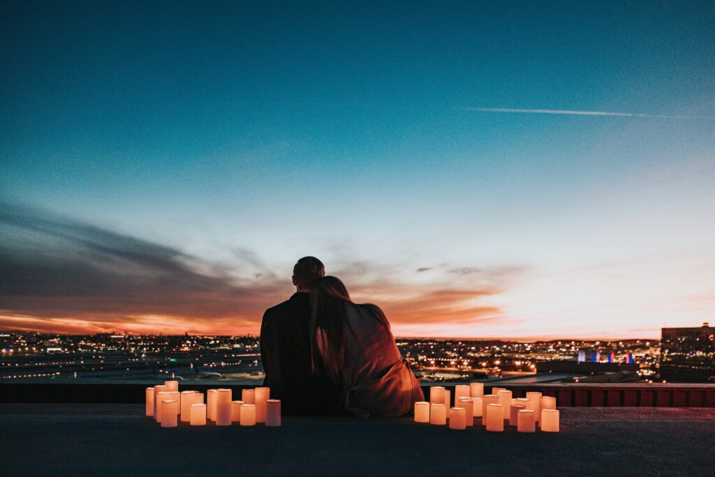 A couple sitting on a high cliff overlooking the city. They have candles on either side of them. They are a dark silhouette