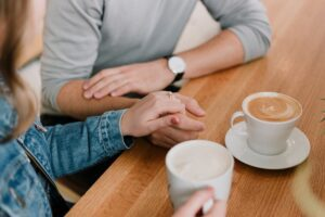 A couple holding hands at a table with coffee. The man is wearing a watch and grey shirt. The lady is wearing a jean jacket.and holding the coffee mug.