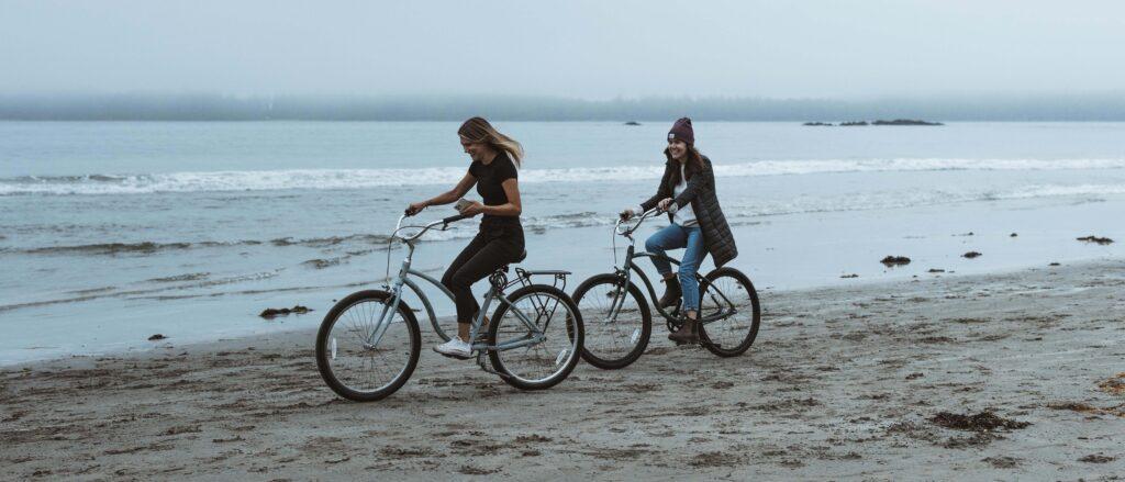 Two girls riding bikes on MacKenzie Beach in Tofino BC