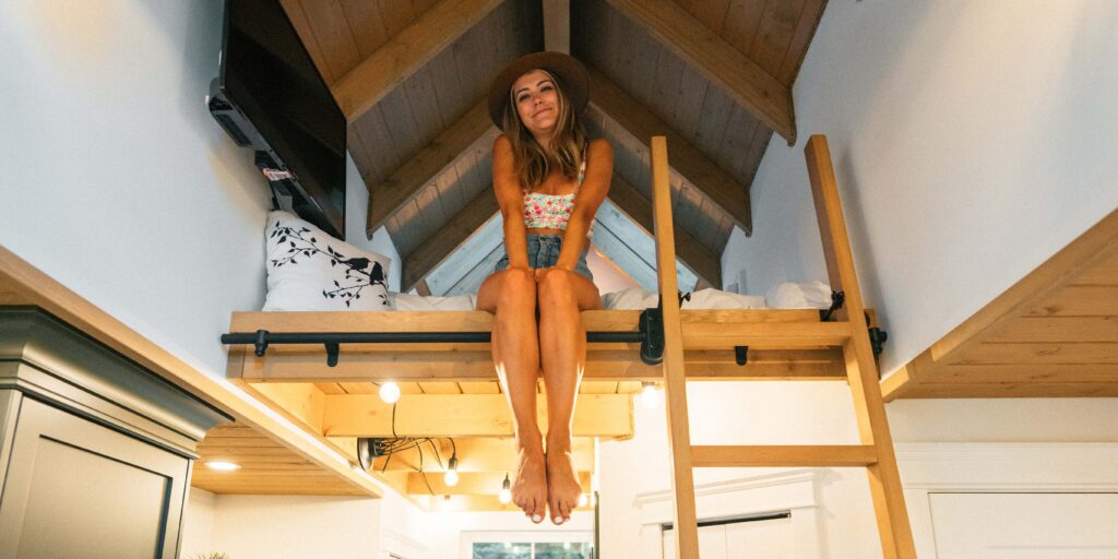 Stay in a treehouse. A girl sitting in a loft bed. Stay in a tree house out in Chilliwack, BC