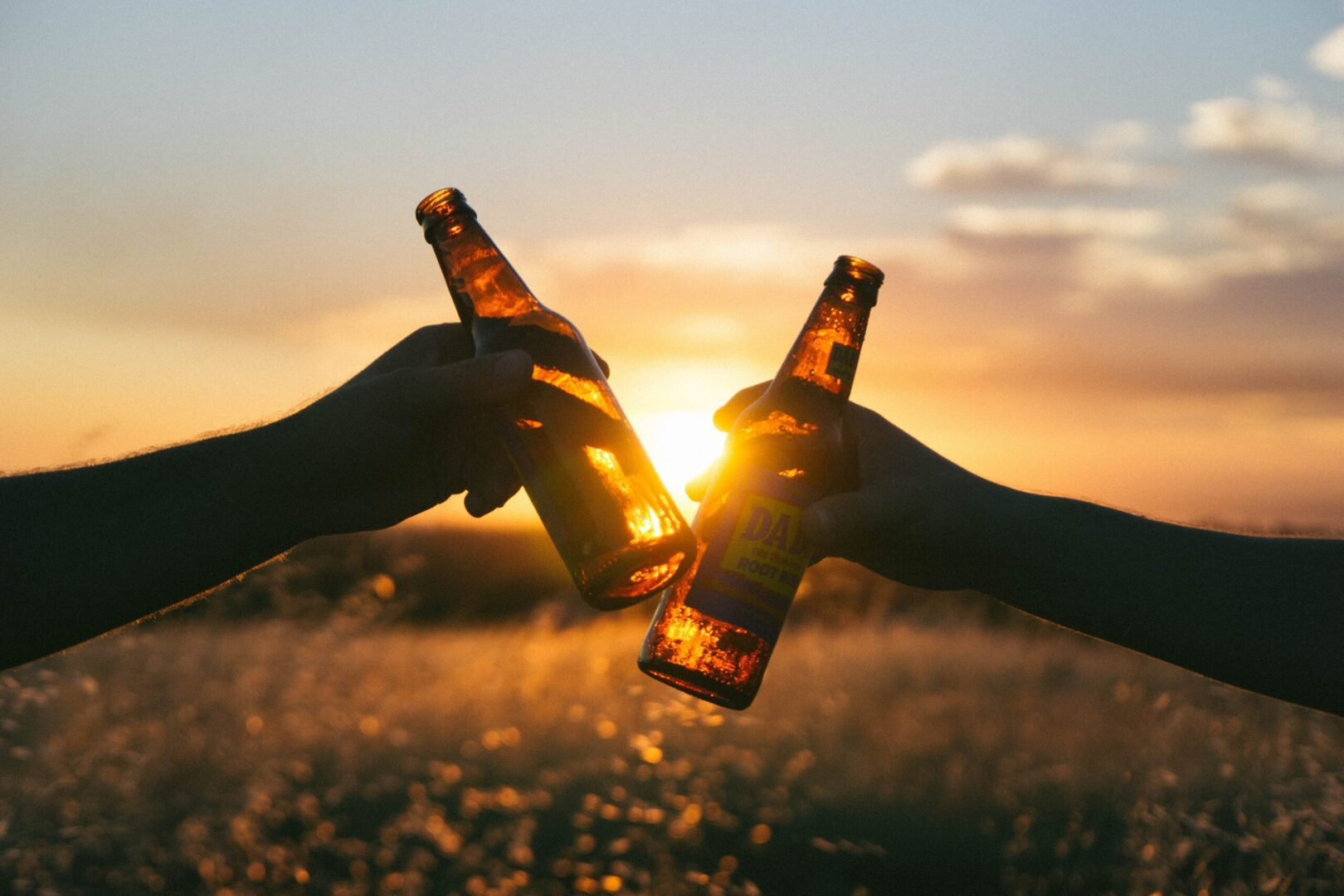 Two beers clinking together in front of a sunset.