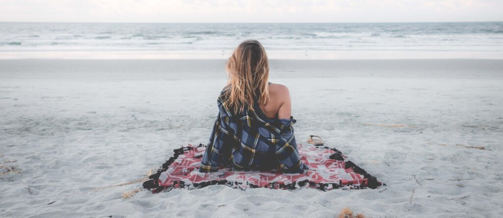 A girl sitting on the beach facing the ocean on a solo date night