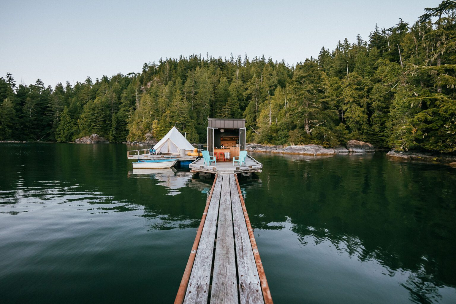 The lagoon float camp in Tofino British Columbia. The water is calm, the sky is blue and you are looking down the dock into the float camp.