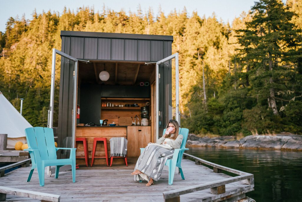 A girl sitting at the lagoon float camp sipping from a pink wine cup.