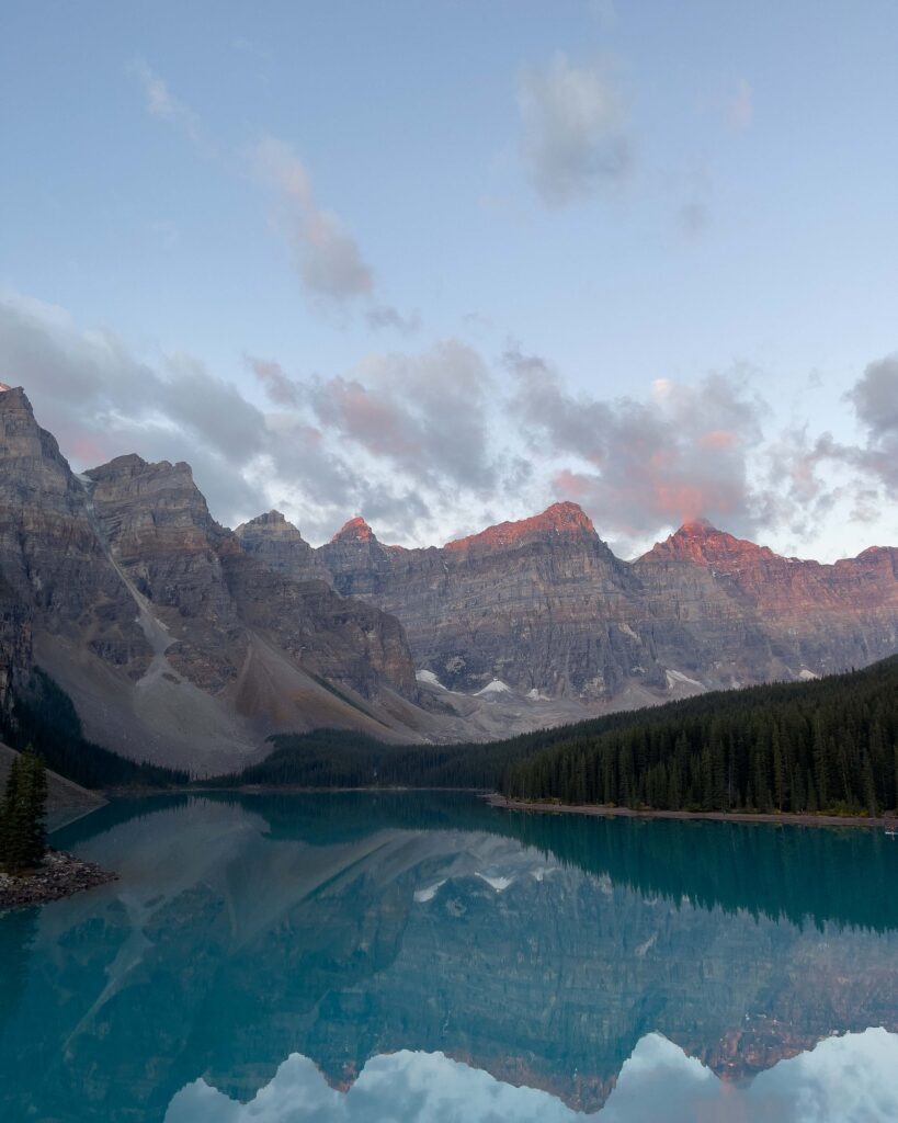 Moraine Lake at Sunrise with koolaid blue water and pink mountain tops.